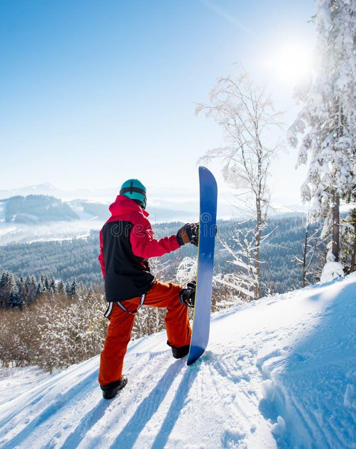 Volledige die lengte van een mannelijke snowboarder status bovenop een helling met zijn snowboard wordt geschoten die rond eruit  royalty-vrije stock foto's