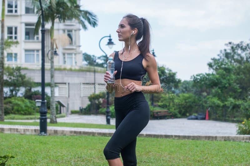 Volledige die lengte van mooi geschiktheids vrouwelijk model wordt geschoten in zwarte sportkleding die zich op gras in stadspark stock foto