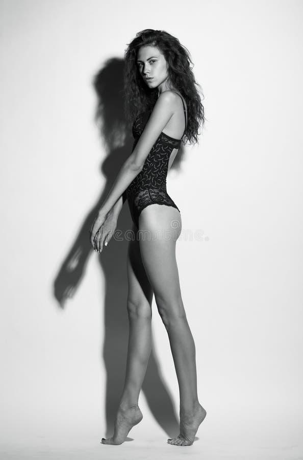 Volledige die lengte van mooie jonge vrouw in zwarte maillot wordt geschoten, blac royalty-vrije stock foto's