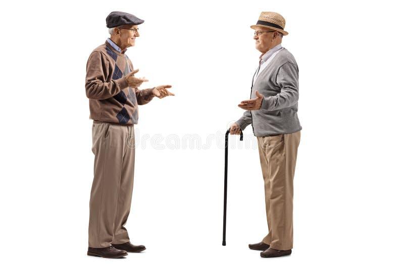Volledige die lengte van twee bejaarden wordt geschoten die een gesprek hebben stock foto's