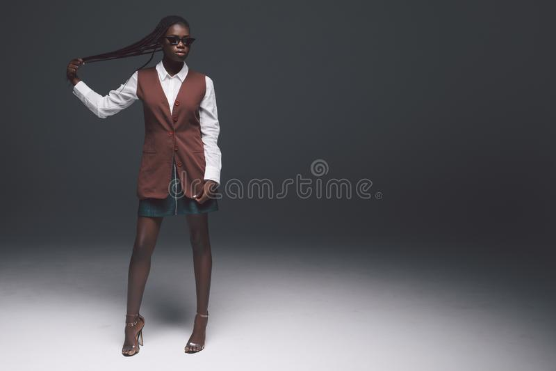 Volledige hoogte jonge Afrikaanse Amerikaanse vrouw met lang donker die haar op donkere achtergrond wordt geïsoleerd royalty-vrije stock afbeelding