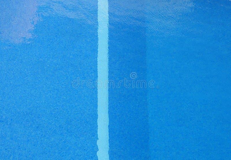 Volledige kader verticale mening van een zwembad met zonovergoten blauw water en rimpelingen met een streep op de tegels die het  royalty-vrije stock foto's
