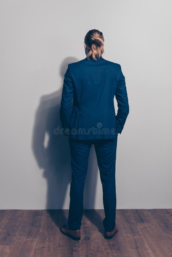 Volledige lengte achtermening van een mens die zich dicht bij grijze muur, wea bevinden stock afbeeldingen