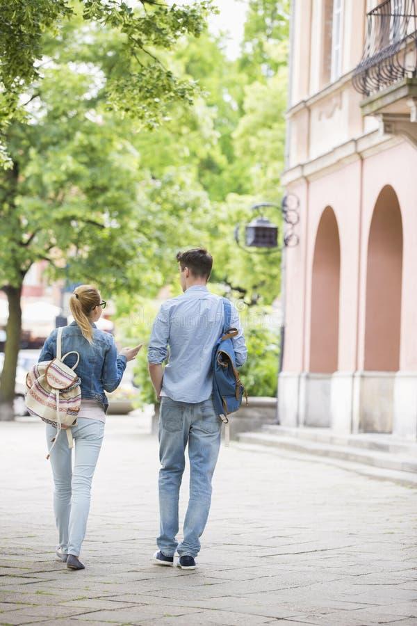 Volledige lengte achtermening van jonge universiteitsvrienden die terwijl het lopen in campus spreken royalty-vrije stock afbeelding