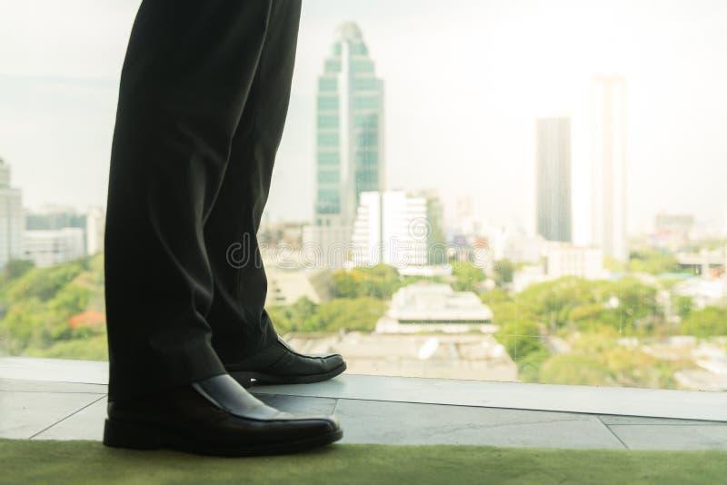 Volledige lengte achtermening van succesvolle zakenman in kostuum dat zich in bureau met handen op zijn taille bevindt stock afbeelding