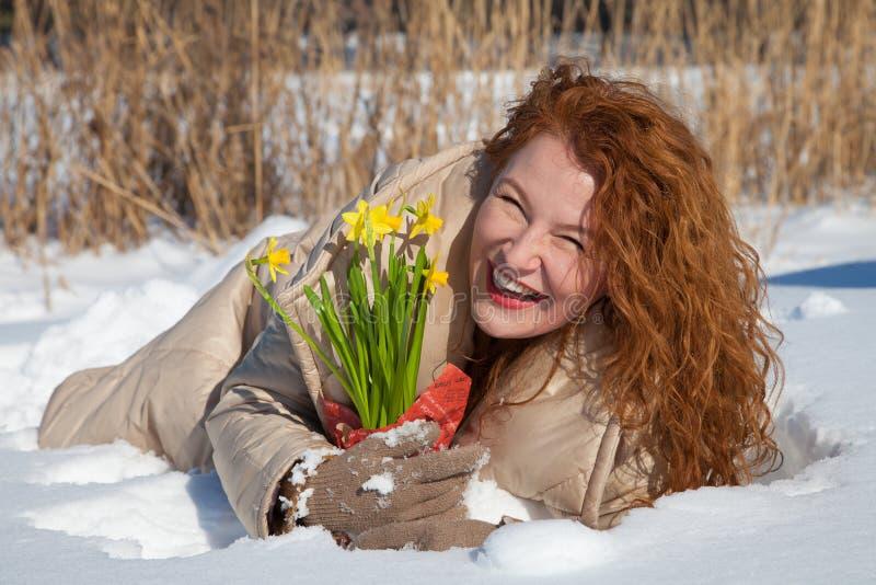 Volledige lengte die van tevreden vrouw op sneeuwoppervlakte liggen met gele narcissuses royalty-vrije stock foto