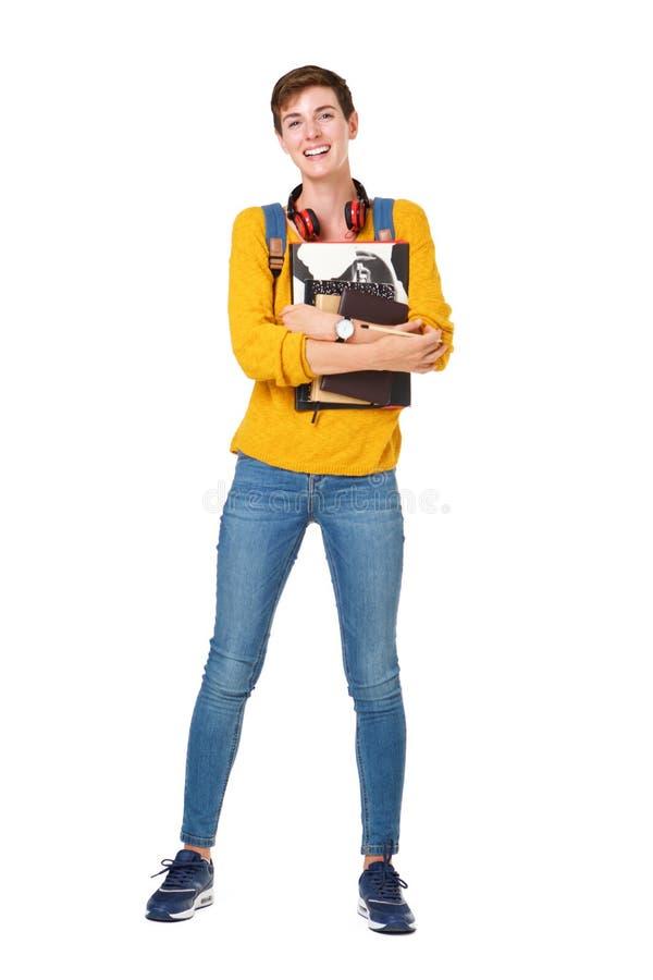 Volledige lengte gelukkige jonge vrouw die zich met zak en boeken tegen geïsoleerde witte achtergrond bevinden royalty-vrije stock foto's