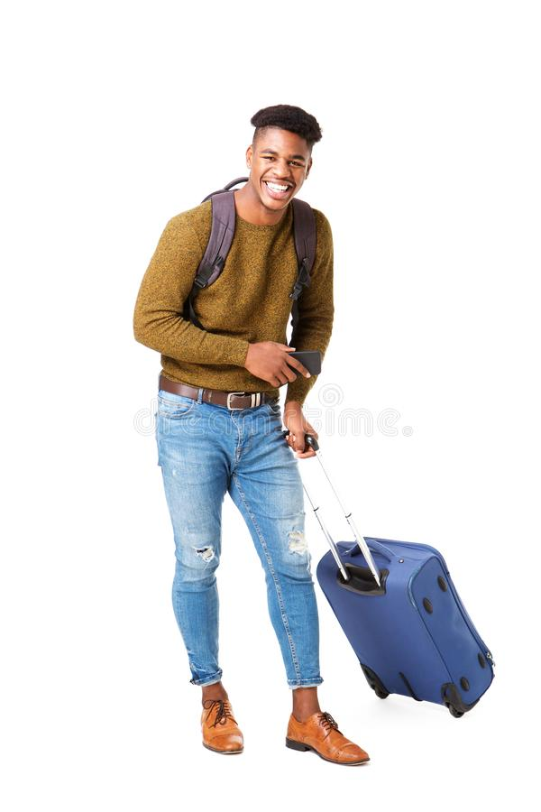 Volledige lengte gelukkige jonge zwarte mens die zich tegen geïsoleerde witte achtergrond met reiszakken en cellphone bevindt stock afbeeldingen