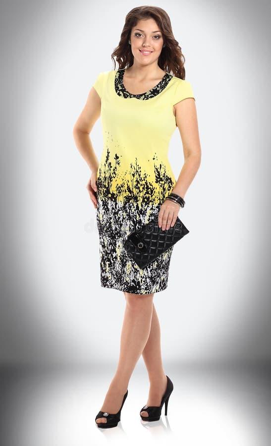 Volledige lengte glimlachende jonge vrouw in gele de zomerkleding stock foto's