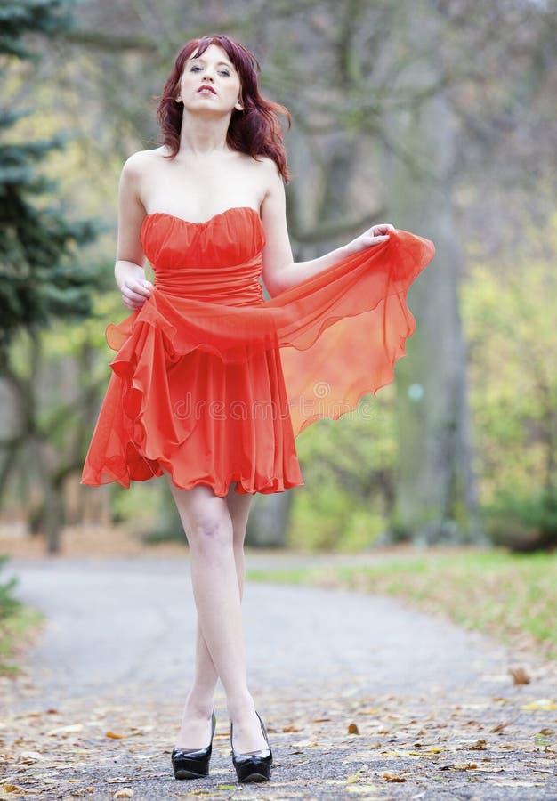 Volledige lengte modieuze vrouw in trillende rode kleding in park royalty-vrije stock fotografie