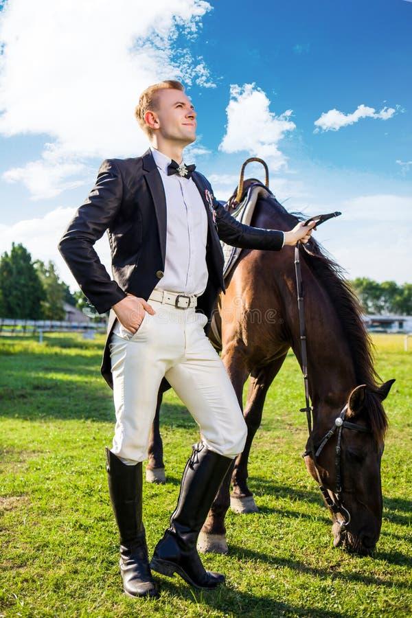 Volledige lengte van de goed-geklede mens die zich door paard op gebied bevinden stock foto's