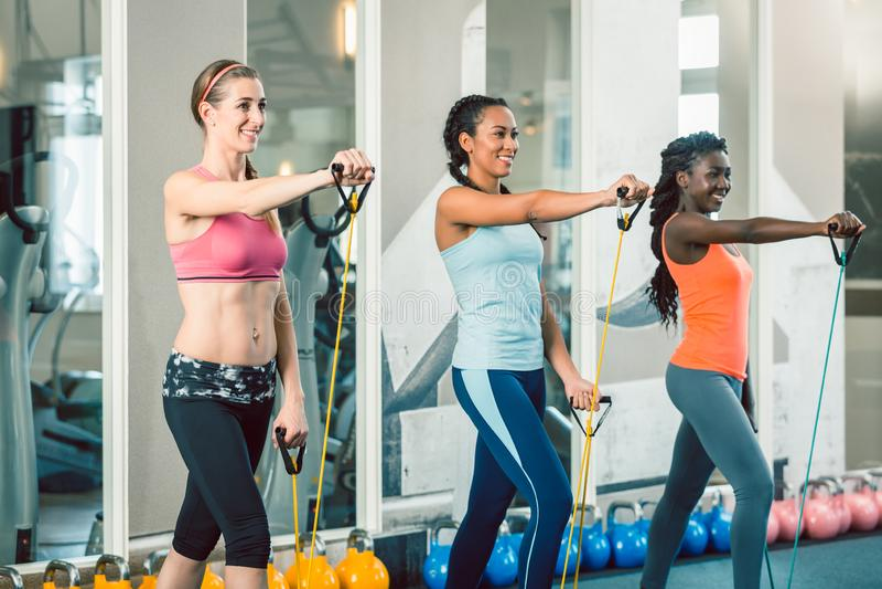 Volledige lengte van drie geschikte vrouwen die met weerstandsbanden uitoefenen stock foto