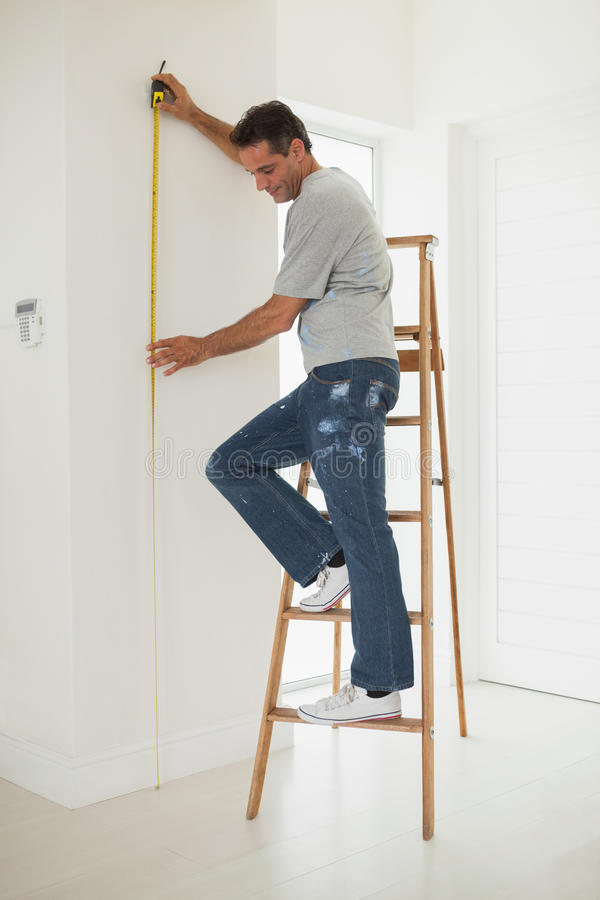Volledige lengte van een mens op ladder terwijl het meten van muur royalty-vrije stock afbeeldingen