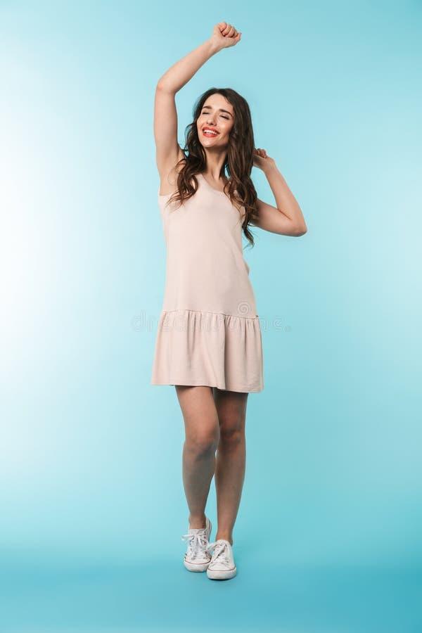 Volledige lengte van een vrolijke jonge donkerbruine vrouw status royalty-vrije stock afbeelding
