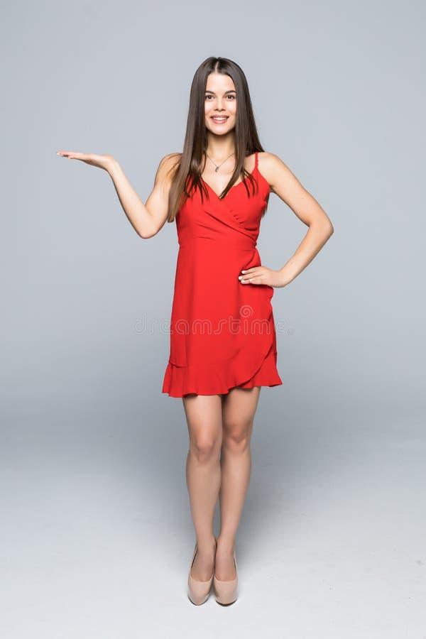 Volledige lengte van gelukkige jonge vrouw die een product tonen - lege exemplaarruimte op de open handpalm, over grijze achtergr royalty-vrije stock fotografie