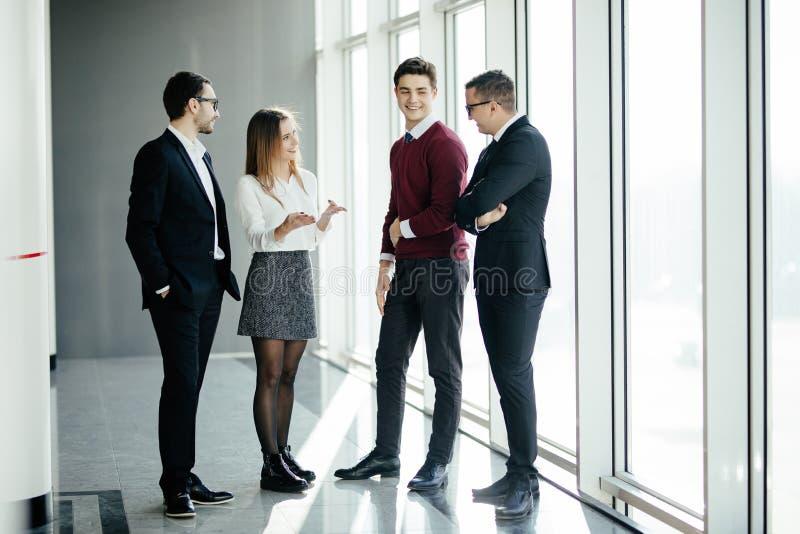 Volledige lengte van groep gelukkige jonge bedrijfsmensen die de zaal in bureau samen lopen stock afbeelding