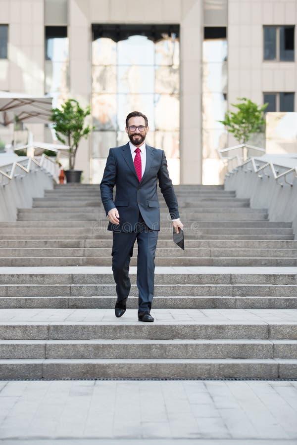 Volledige lengte van het bloeiende zakenman lopen onderaan de treden buiten het bureaugebouw stock foto