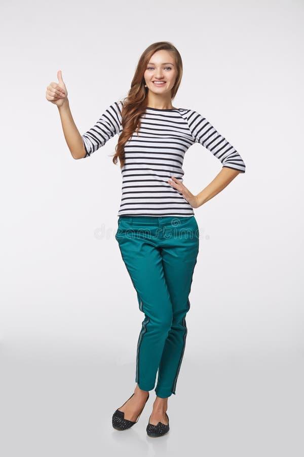 Volledige lengte van jong leuk glimlachend emotioneel meisje die u thum geven royalty-vrije stock foto's