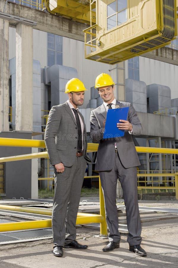 Volledige lengte van jonge zakenlieden met klembord die bij bouwwerf bespreken stock fotografie