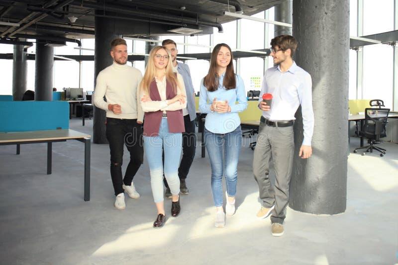 Volledige lengte van jongeren in slimme zaken bespreken en vrijetijdskleding die terwijl het lopen door het bureau glimlachen royalty-vrije stock foto's