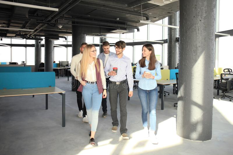 Volledige lengte van jongeren in slimme zaken bespreken en vrijetijdskleding die terwijl het lopen door het bureau glimlachen stock afbeelding