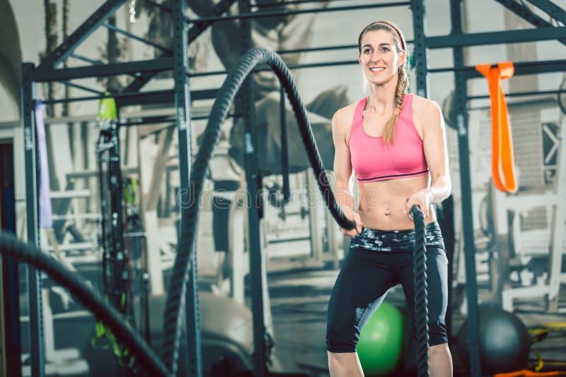 Volledige lengte van kabels van een de sterke en mooie vrouwen golvende slag bij de gymnastiek royalty-vrije stock afbeeldingen