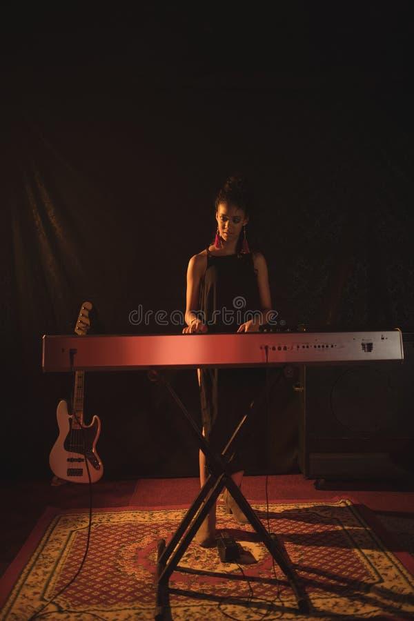 Volledige lengte van musicus het spelen piano in nachtclub stock afbeelding