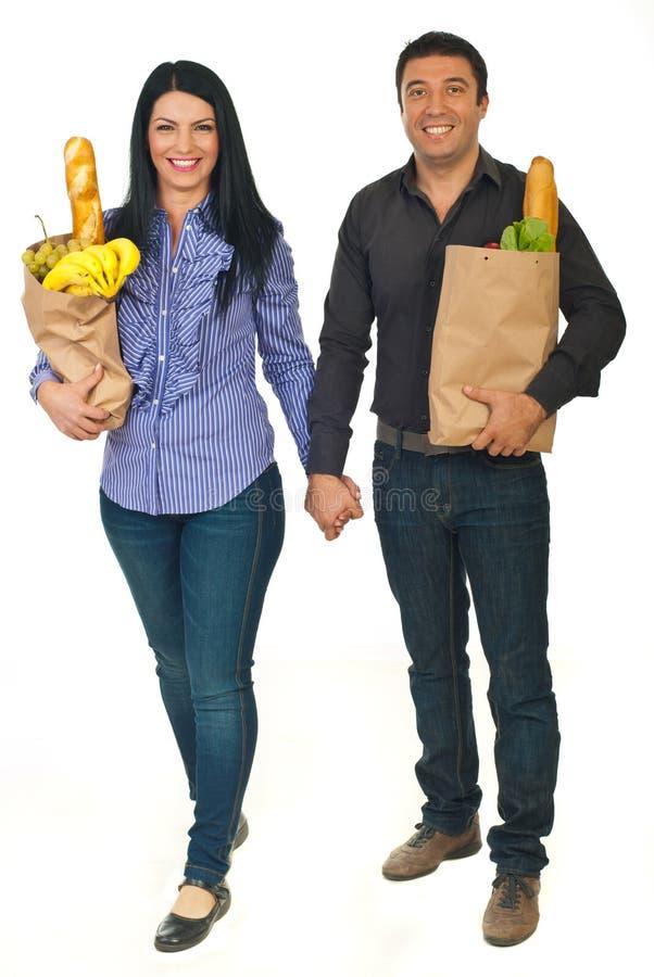 Volledige lengte van paar dragende zakken met voedsel stock afbeelding