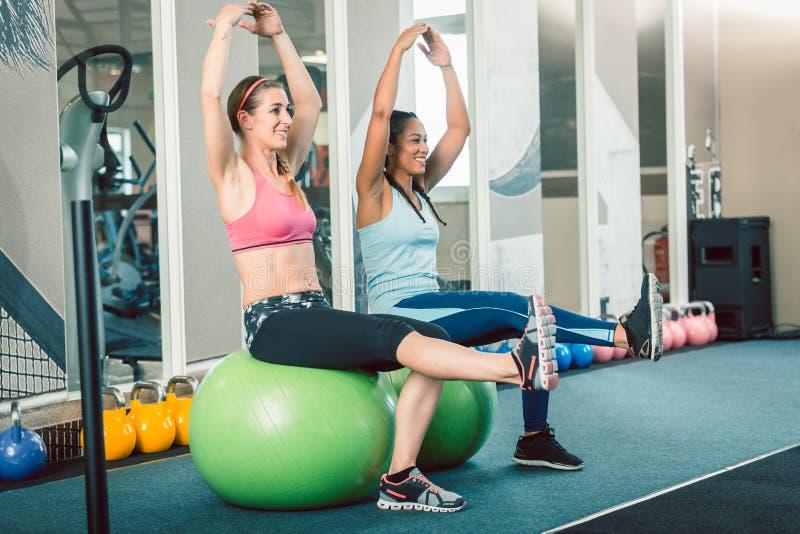 Volledige lengte van twee geschikte vrouwen die op geschiktheidsballen zitten terwijl het uitoefenen royalty-vrije stock foto's