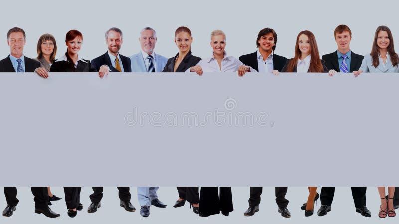 Volledige lengte van vele bedrijfsmensen die op een rij een lege banner op witte achtergrond houden stock foto's