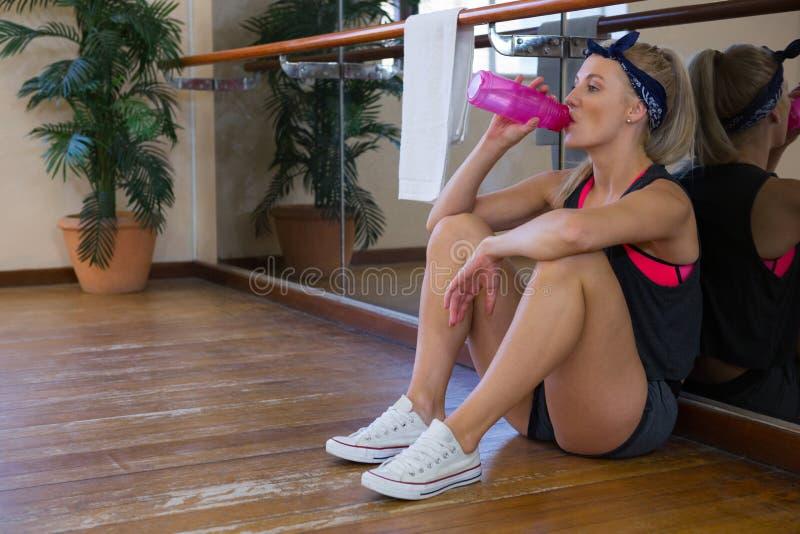Volledige lengte van vermoeid vrouwelijk dansers drinkwater bij studio royalty-vrije stock afbeeldingen