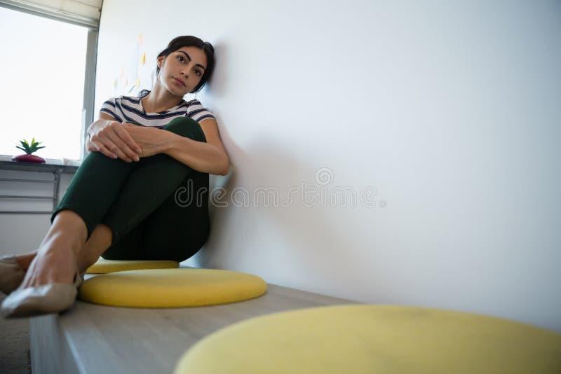 Volledige lengte van vermoeide vrouw door muur op zetel in bureau stock foto