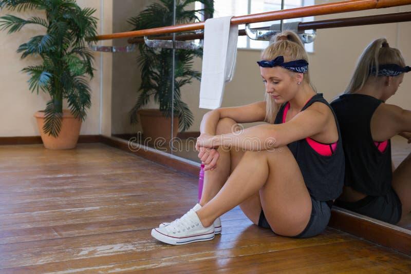 Volledige lengte van vermoeide vrouwelijke danserszitting bij studio stock foto
