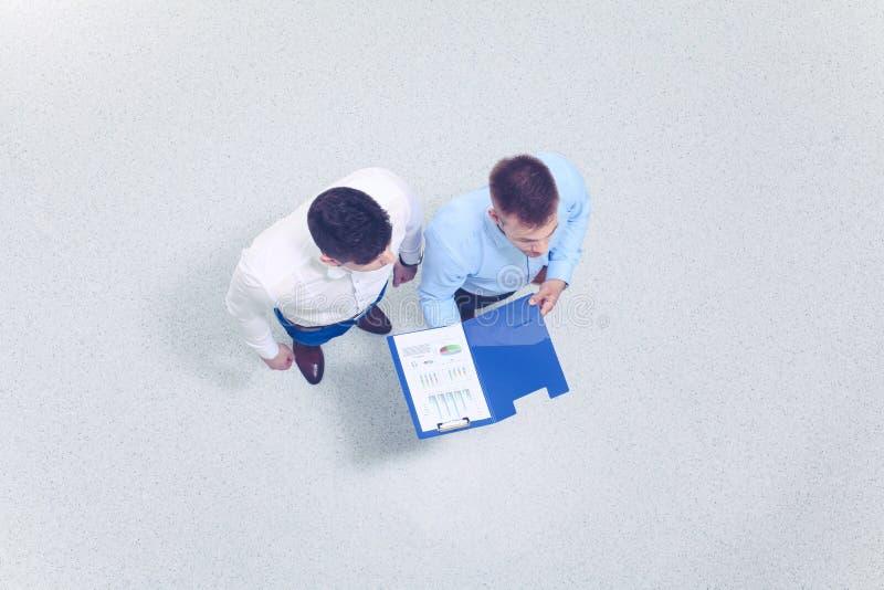 Volledige lengte van zakenlieden met bedrijfsdiecontract op witte achtergrond wordt ge?soleerd stock fotografie