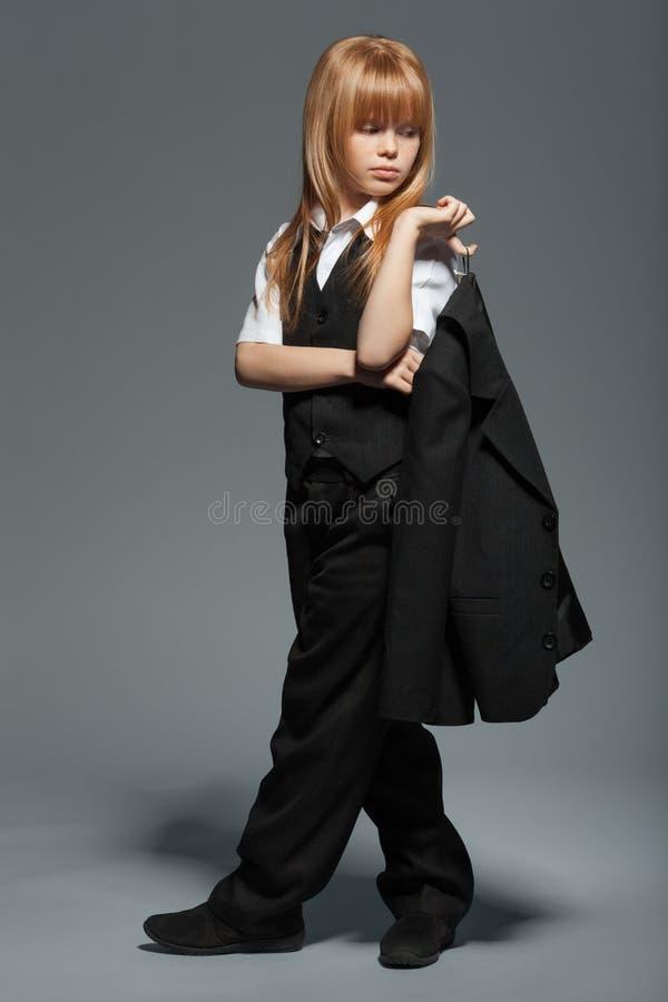 Volledige lengte weinig leuk meisje in zwart kostuum, met een jasje in zijn die handen, over grijze achtergrond worden geïsoleerd stock fotografie