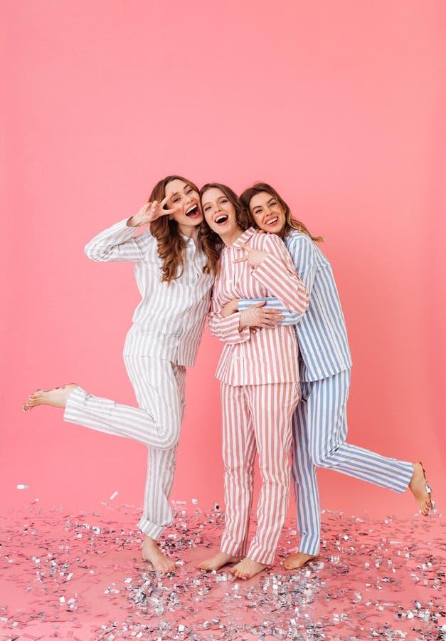 Volledige lengtefoto die van drie mooie tienervrouwenjaren '20 l dragen stock foto