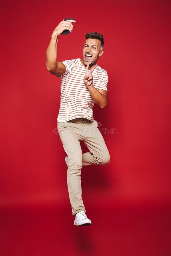 Volledige lengtefoto van de donkerbruine mens in gestreepte t-shirt die springen en stock afbeeldingen