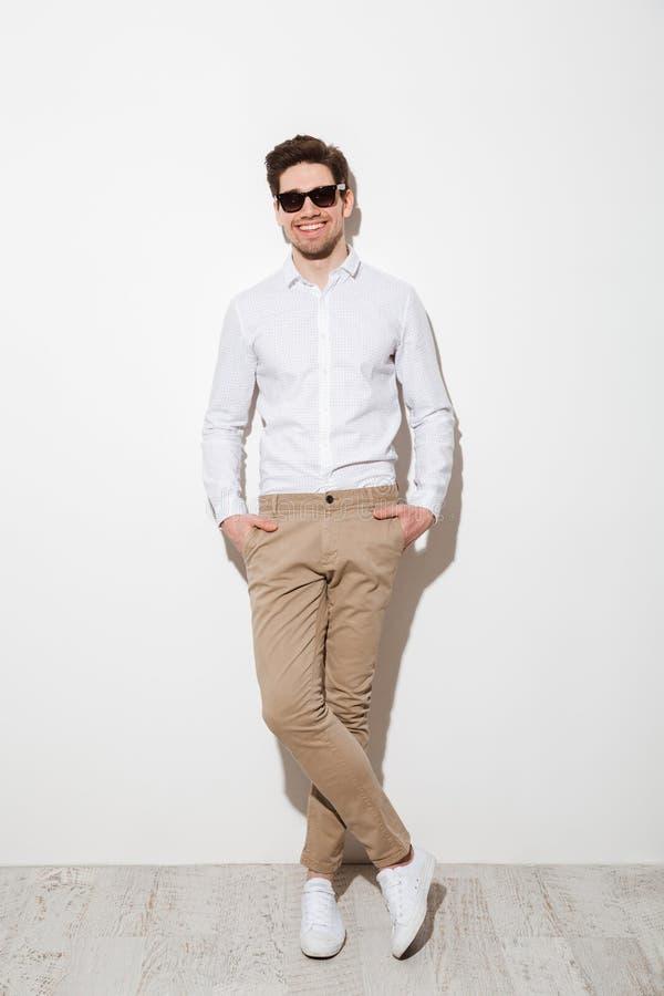 Volledige lengtefoto van knappe kerel gekleed in toevallige kleding en stock foto