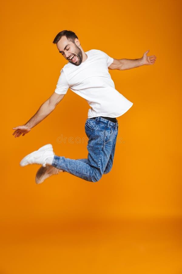 Volledige lengtefoto van positieve kerel in t-shirt en jeans die en pret, over gele achtergrond springen hebben royalty-vrije stock foto