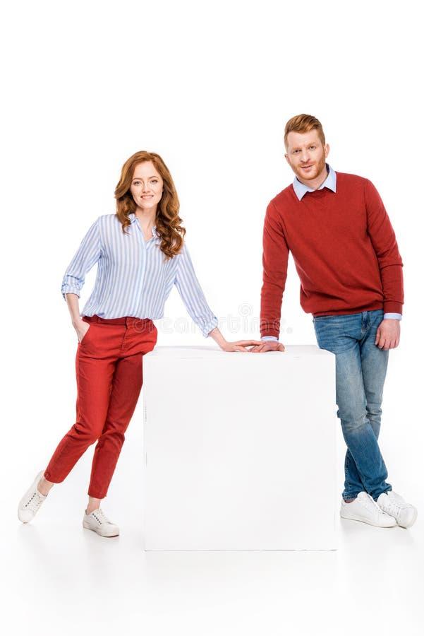 volledige lengtemening van gelukkig roodharigepaar die bij witte kubus leunen en bij camera glimlachen royalty-vrije stock afbeelding