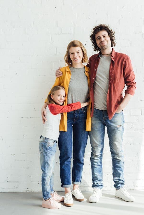 volledige lengtemening van gelukkige ouders met dochter het omhelzen en het glimlachen stock fotografie