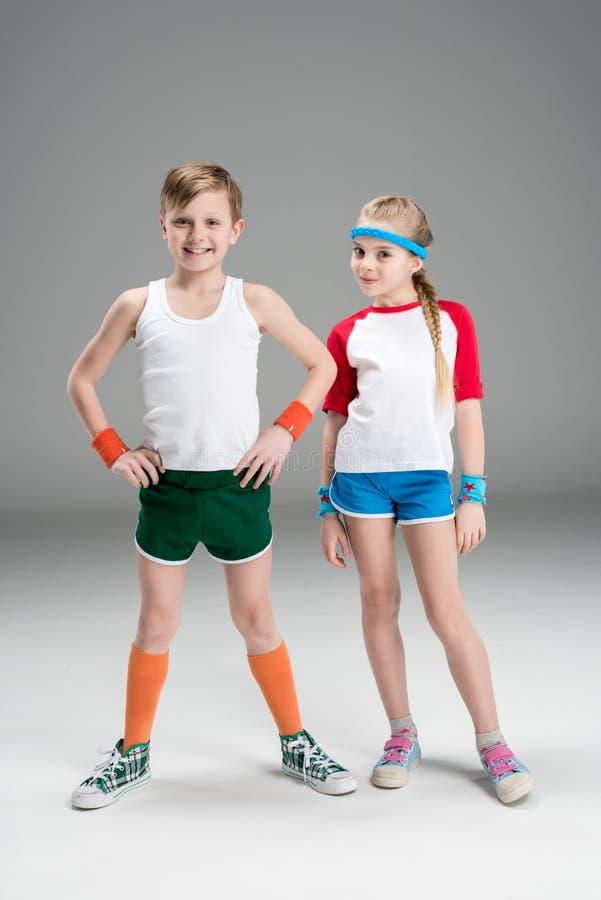 Volledige lengtemening van leuk glimlachend jongen en meisje in sportkleding die zich op grijs verenigen royalty-vrije stock foto's