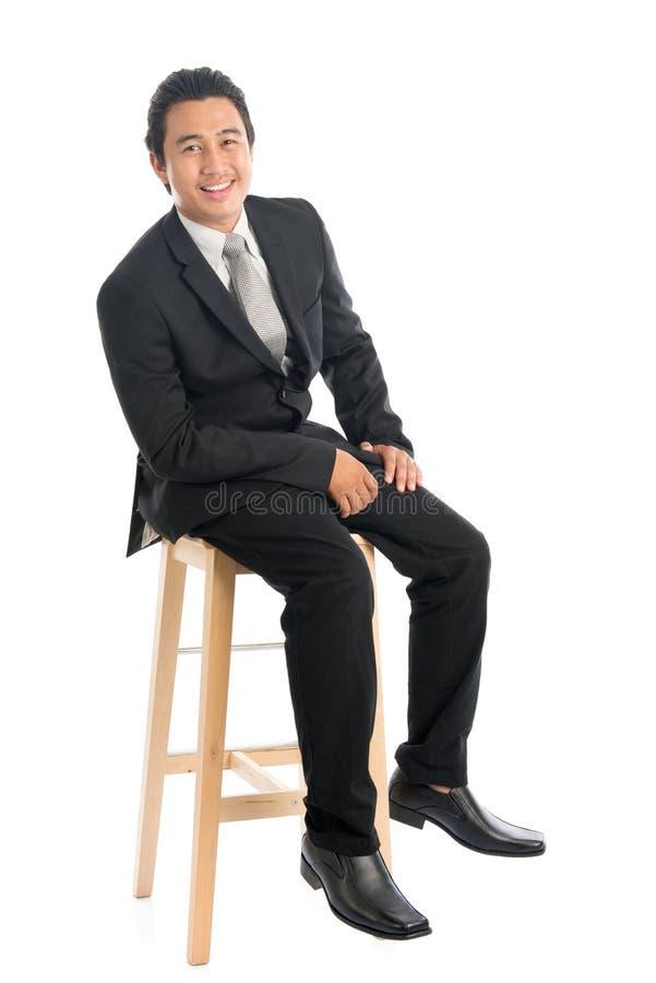 Volledige lichaams Aziatische zakenman gezet op hoge stoel royalty-vrije stock foto