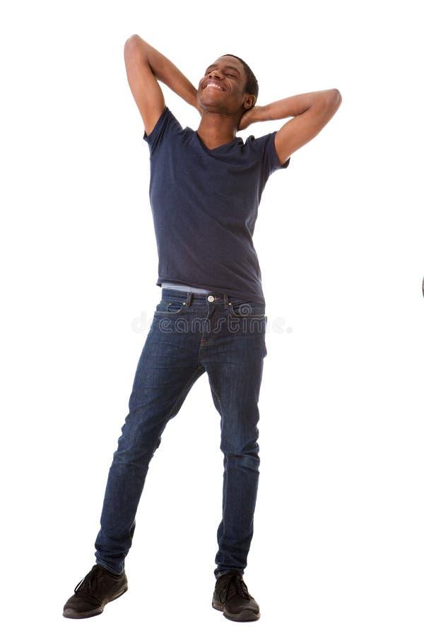 Volledige lichaams gelukkige Afrikaanse Amerikaanse mens die zich met handen achter hoofd op geïsoleerde witte achtergrond bevind stock foto