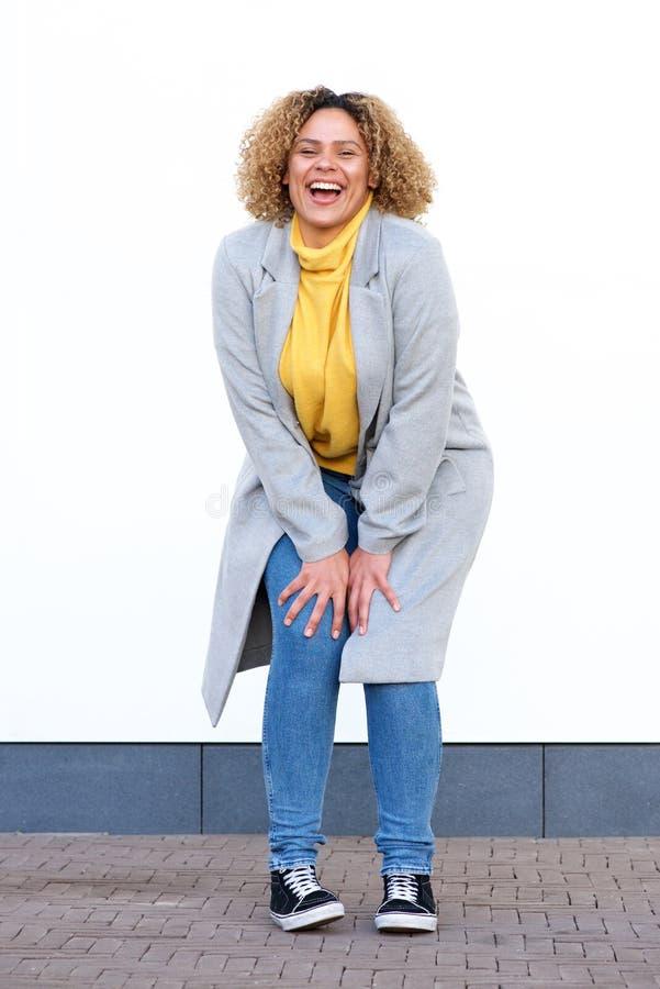 Volledige lichaams gelukkige jonge Afrikaanse Amerikaanse vrouw die in de winterlaag door witte muur lachen stock afbeeldingen