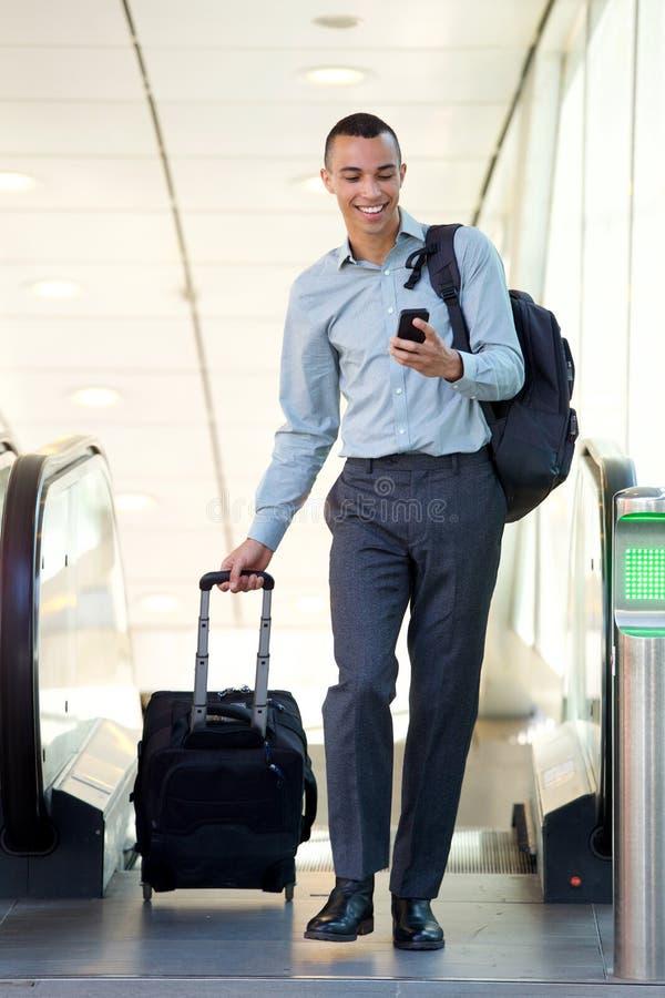 Volledige lichaams jonge zakenman die met reiszakken en mobiele telefoon lopen stock foto