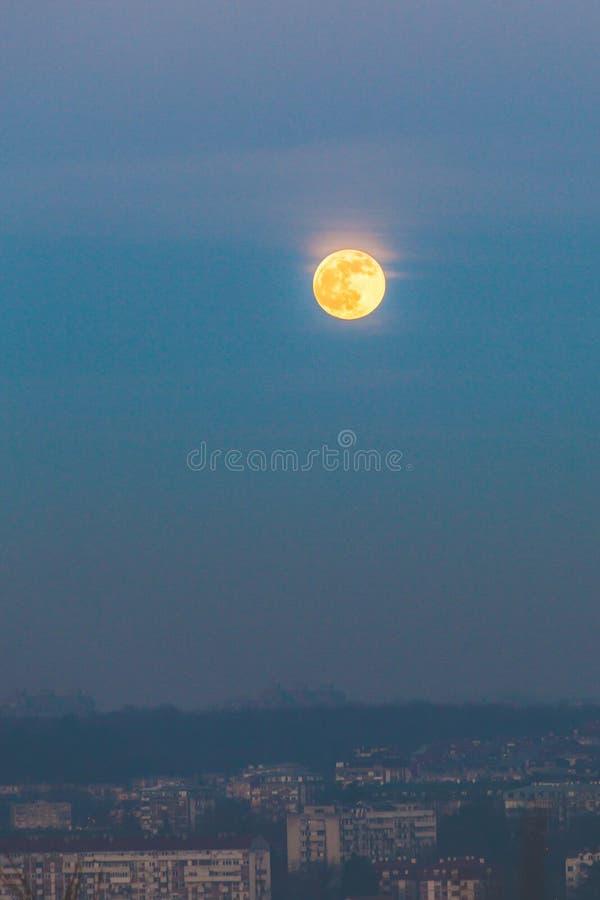 Volledige maan bij zonsondergang boven de vervuilde stad Belgrado stock foto