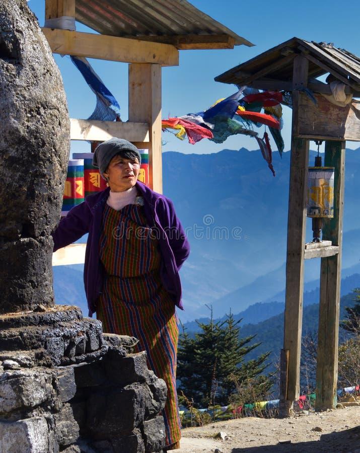 Volledige Potrait van een oude vrouw Uit Bhutan in traditionele kleding naast het godsdienstige spinnewiel bij Chele-La, Paro, Bh royalty-vrije stock afbeeldingen
