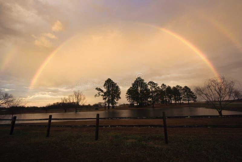 Volledige regenboog bij zonsondergang stock fotografie