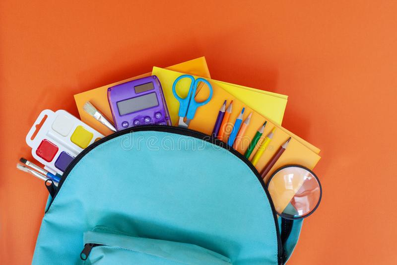 Volledige turkooise Schoolrugzak met verschillende levering op oranje achtergrond Vlak leg Concept terug naar school stock fotografie